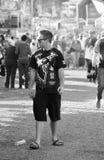 Osamotniony młody nastoletni mężczyzna stoi out od tłumu przy karnawałem zdjęcie royalty free