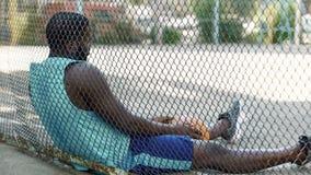 Osamotniony nierad mężczyzna obsiadanie przy boisko do koszykówki i mienia piłką, depresja obrazy stock