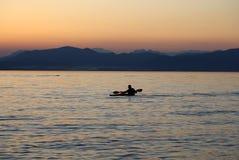 Osamotniony paddler na jeziorze podczas zmierzchu Fotografia Royalty Free