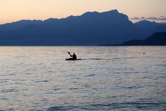 Osamotniony paddler na jeziorze podczas zmierzchu Obrazy Stock