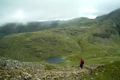 Osamotniony piechur pochodzi od Wielkiego szczytu Styhead Tarn Zdjęcie Stock