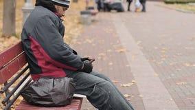 Osamotniony pijący mężczyzna ka na ławce, trzyma butelkę z piwem, alkoholu nałóg zbiory
