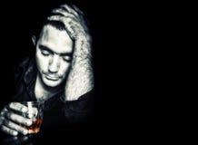 Osamotniony pijący mężczyzna na czarnym tle obrazy royalty free