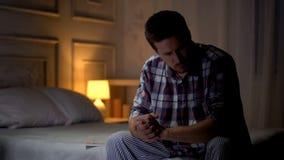 Osamotniony smutny mężczyzny obsiadanie na łóżku, doświadcza bolesną żony stratę, żal i stroskanie, zdjęcie royalty free