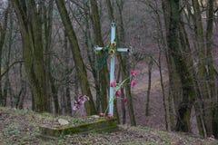 Osamotniony stary grób z attificial kwiatami w parkowym terenie Obrazy Stock