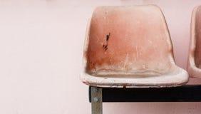 Osamotniony stary krzesło na menchii ściany tle Obraz Royalty Free