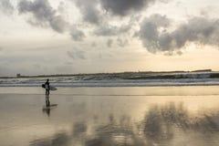 Osamotniony surfingowiec przy zmierzchem w pustynnej plaży Obrazy Stock