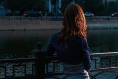 Osamotniony weekend Czerwona z włosami dziewczyna patrzeje nocy rzekę w miasto parku obraz royalty free