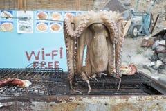 OSantorini octopus. An octopus hangs above a grill at an open air cafe on Thirasia island, Santorini stock images