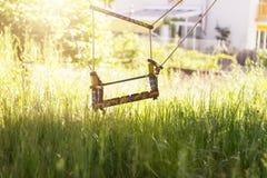 Oscilación abandonado en la alta hierba en la estación de primavera Fotos de archivo