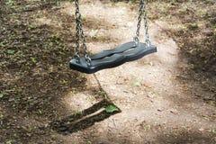 Oscilación abandonado en un ambiente del parque con condiciones hermosas de la luz y de la sombra fotos de archivo