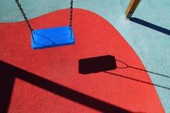 Oscilación azul del parque o patio rojo de los niños del suelo Imagenes de archivo