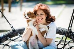 Oscilación de la mujer con su perro imagenes de archivo
