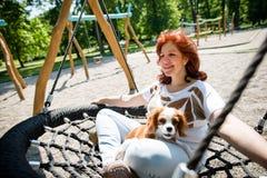Oscilación de la mujer con su perro foto de archivo