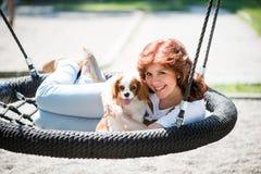 Oscilación de la mujer con su perro fotos de archivo libres de regalías