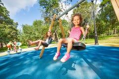 Oscilación de los niños en patio Foto de archivo libre de regalías
