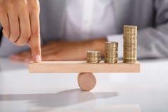 Oscilación de madera de Balancing Coins On del empresario fotografía de archivo