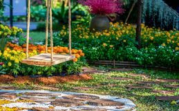 Oscilación de madera colgante dentro del jardín de flores imágenes de archivo libres de regalías