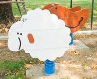 Oscilación de madera de la primavera de las ovejas en patio del niño Imagen de archivo libre de regalías