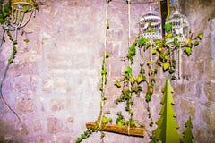 Oscilación de madera y jaulas de pájaros que cuelgan en una pared de piedra con las hojas verdes Fotografía de archivo libre de regalías