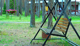 Oscilación del jardín cerca de una casa en una madera de pino imagen de archivo libre de regalías