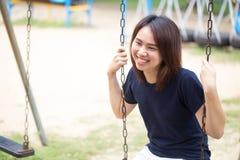 Oscilación del juego del desgaste que se sienta de la sonrisa casual adolescente sana asiática del paño Imágenes de archivo libres de regalías