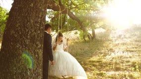 Oscilaci?n del muchacho y de la muchacha en una rama de un roble en el novio feliz del bosque del verano que balancea en un oscil almacen de metraje de vídeo