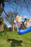 Oscilación del niño en jardín fotos de archivo