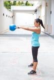 Oscilación hispánico de la mujer del deporte el kettlebell azul, al aire libre Imagen de archivo libre de regalías