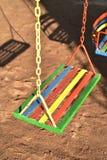 Oscilación pintado multicolor para el niño en patio Imágenes de archivo libres de regalías