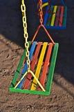 Oscilación pintado multicolor para el niño en patio Fotografía de archivo libre de regalías