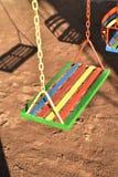 Oscilación pintado multicolor para el niño en patio Foto de archivo libre de regalías