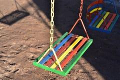 Oscilación pintado multicolor para el niño en patio Fotos de archivo libres de regalías