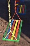 Oscilación pintado multicolor para el niño en patio Foto de archivo