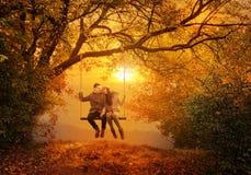 Oscilación romántico de los pares en el parque del otoño