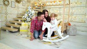 Oscilaciones de la ni?a en caballo mecedora al lado de sus padres cerca del ?rbol de navidad metrajes