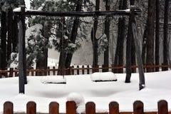 Oscilaciones de los niños cubiertos con nieve imagen de archivo