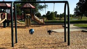 Oscilaciones vacíos de los niños que se mueven en patio almacen de metraje de vídeo