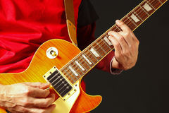 Oscile al guitarrista que toca la guitarra eléctrica en fondo oscuro Fotos de archivo