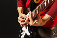 Oscile al músico con la guitarra eléctrica en fondo negro Imágenes de archivo libres de regalías