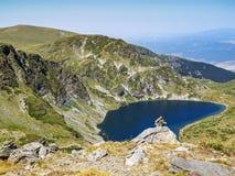 Oscile el equilibrio, roca que apila delante de uno de los siete lagos Rila en las montañas de Rila, Bulgaria Foto de archivo