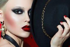Oscile a la muchacha en un sombrero negro con los labios rojos Fotos de archivo
