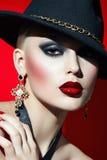Oscile a la muchacha en un sombrero negro con los labios rojos Foto de archivo