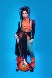 Oscile a la muchacha que presenta con la guitarra eléctrica en backgroun azul Fotos de archivo
