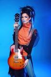 Oscile a la muchacha que presenta con la guitarra eléctrica en backgroun azul Foto de archivo
