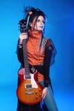 Oscile a la muchacha que presenta con la guitarra eléctrica en backgroun azul Imagenes de archivo
