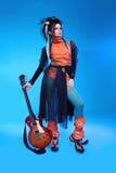 Oscile a la muchacha que presenta con la guitarra eléctrica en backgroun azul Imagen de archivo libre de regalías