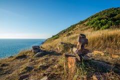 Oscile la raya en la posición vertical respecto a la montaña del campo de hierba al lado del mar Imágenes de archivo libres de regalías
