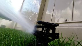 Oscillating lawn sprinkler watering grass Royalty Free Stock Photography