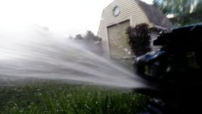 Oscillating lawn sprinkler watering grass Royalty Free Stock Photos